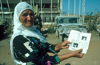A Palestinian mother shows her missing son's papers, Sabra - Shatilla